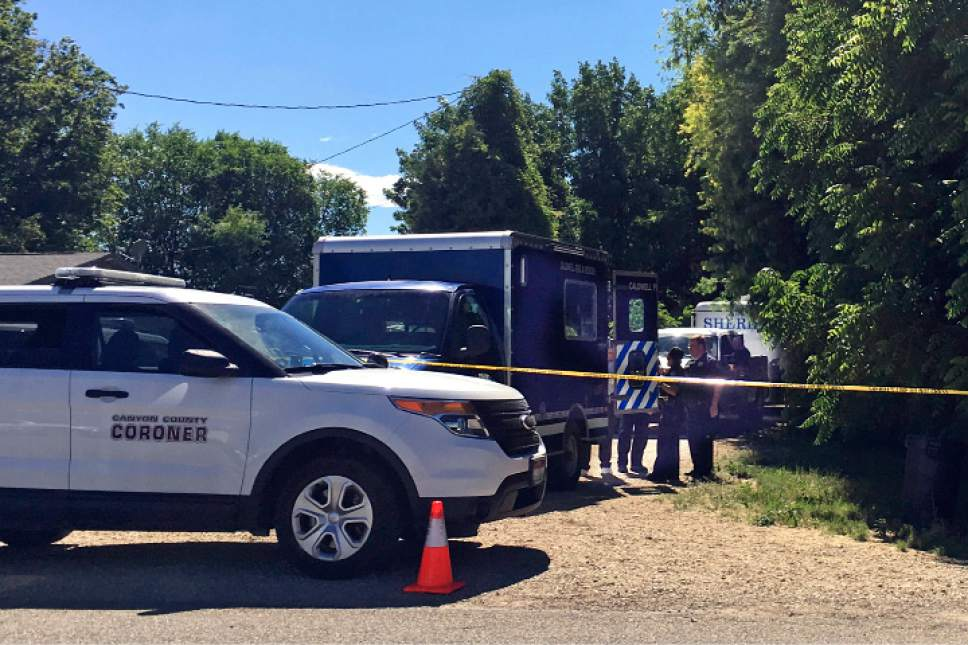 Kimberlee Kruesi  |  The Associated Press Authorities investigate a scene in Caldwell, Idaho, last week. Police say three people were found dead inside a home and the Canyon County Sheriff's office is investigating the deaths as possible homicides.