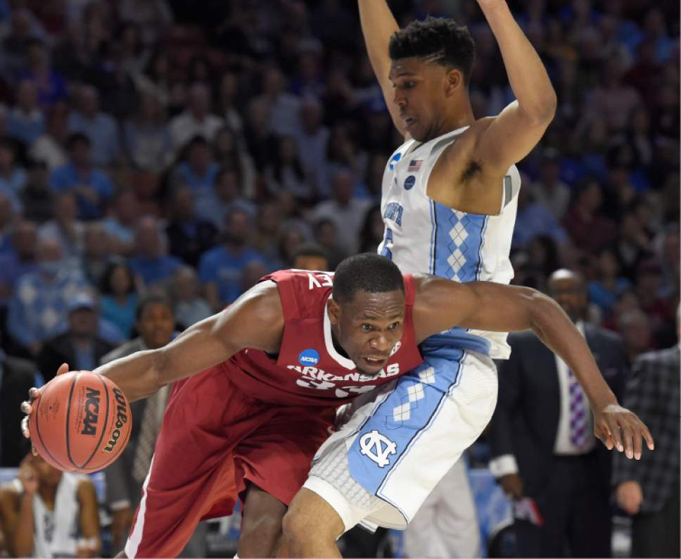 Arkansas' Moses Kingsley (33) drives around North Carolina's Tony Bradley (5) during the first half in a second-round game of the NCAA men's college basketball tournament in Greenville, S.C., Sunday, March 19, 2017. (AP Photo/Rainier Ehrhardt)