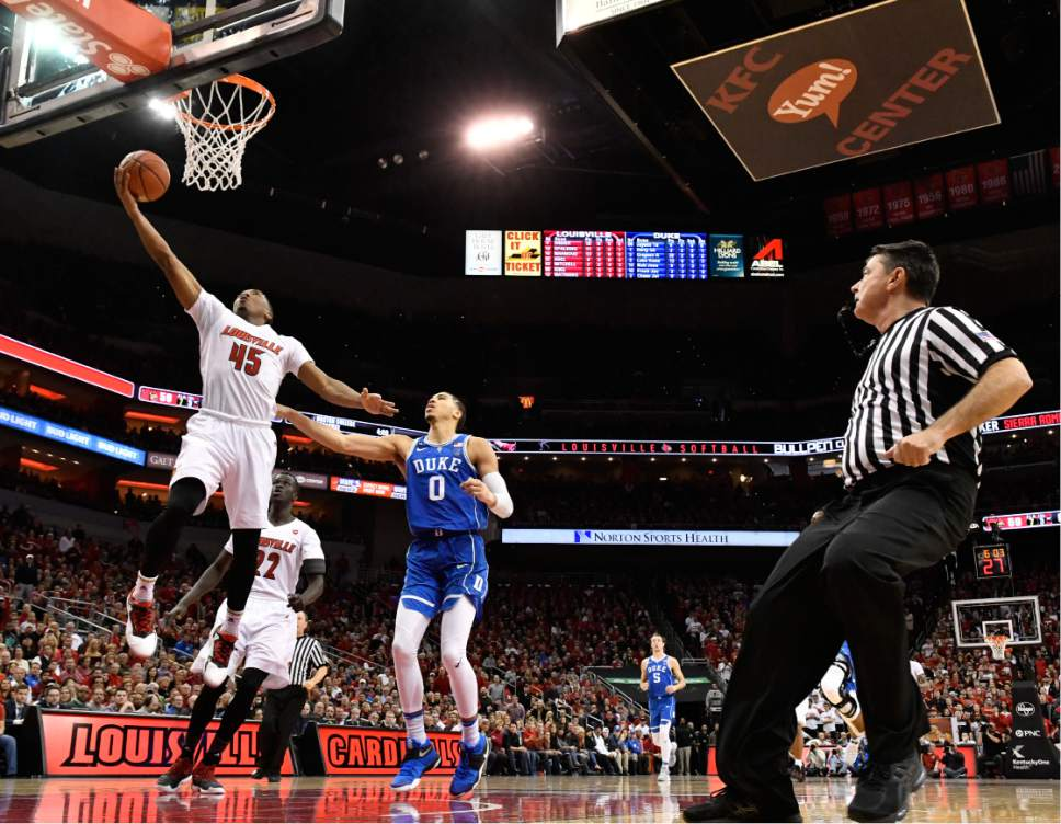 Louisville's Donovan Mitchell (45) goes in for a layup ahead of Duke's Jayson Tatum (0) during the second half of an NCAA college basketball game, Saturday, Jan. 14, 2017, in Louisville, Ky. Louisville won 78-69. (AP Photo/Timothy D. Easley)