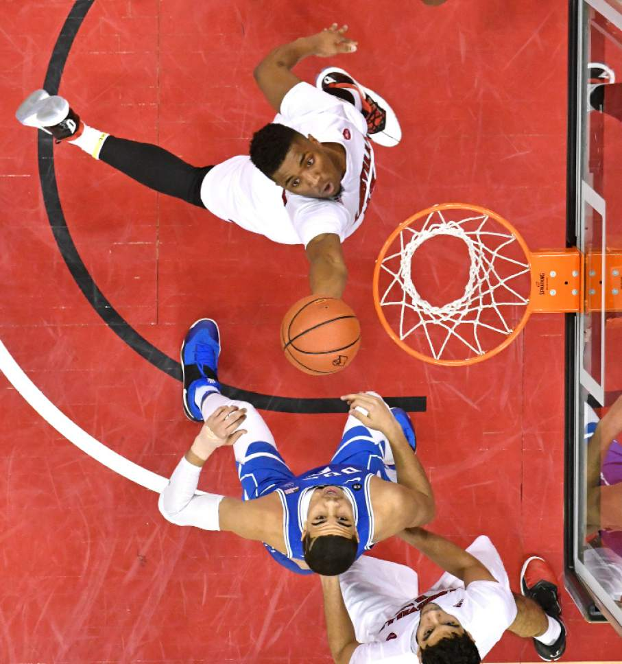 Louisville's Donovan Mitchell, top, goes in for a layup past the defense of Duke's Jayson Tatum (0) during the second half of an NCAA college basketball game, Saturday, Jan. 14, 2017, in Louisville, Ky. Louisville won 78-69. (AP Photo/Timothy D. Easley)