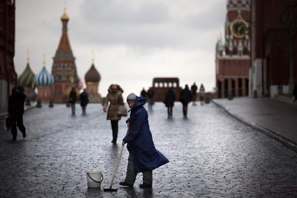 A street worker cleans paving stones in Red Square with St. Basil's Cathedral, left, Lenin Mausoleum,  center, and the Spasskaya Tower, right, in Moscow, Russia, Tuesday, Dec. 22, 2015. (AP Photo/Alexander Zemlianichenko)