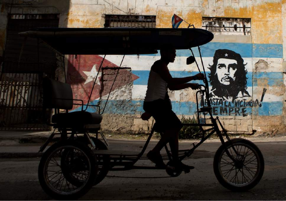 """A bicycle taxi rides past a building painted with a Cuban flag and an image of Che Guevara, along with the Spanish slogan """"Always toward victory!"""" in Havana, Cuba, Saturday, March 19, 2016. U.S. President Barack Obama will visit the island on March 20. During his three-day trip, the first to the country by a sitting U.S. president in nearly 90 years, he will meet with President Raul Castro at the Palace of the Revolution and attend an exhibition baseball game. (AP Photo/Rebecca Blackwell)"""