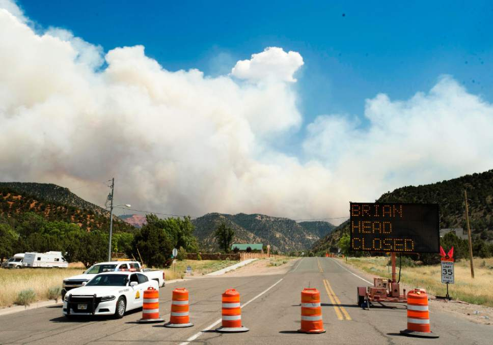 Rick Egan  |  The Salt Lake Tribune Smoke billows in the afternoon winds behind the roadblock closing highway 143 to Brian Head, in Parowan on Wednesday.