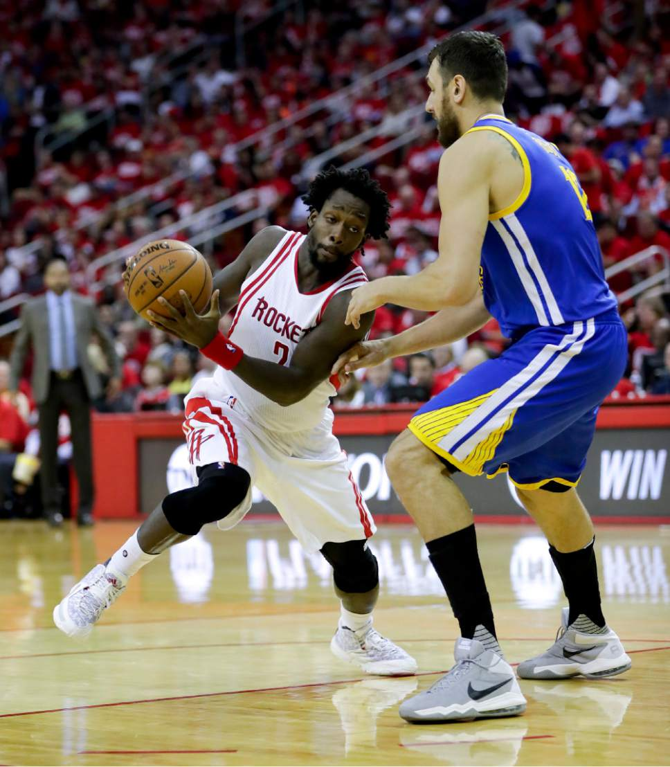 Houston Rockets guard Patrick Beverley, left, drives to the basket around Golden State Warriors center Andrew Bogut during the first half in Game 3 of a first-round NBA basketball playoff series, Thursday, April 21, 2016, in Houston. (AP Photo/David J. Phillip)