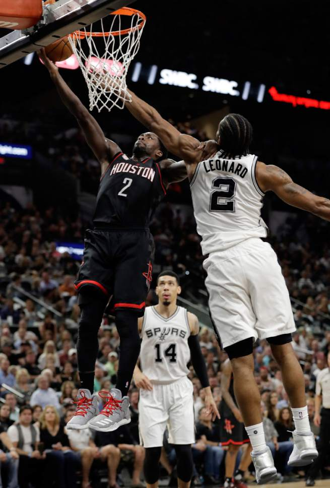 Houston Rockets guard Patrick Beverley (2) goes up for a shot as San Antonio Spurs' Danny Green (14) and Kawhi Leonard (2) defend during the first half of Game 2 in a second-round NBA basketball playoff series, Wednesday, May 3, 2017, in San Antonio. (AP Photo/Eric Gay)
