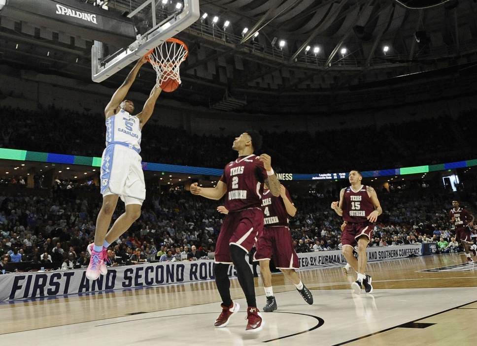 North Carolina's Tony Bradley (5) dunks against Texas Southern's Zach Lofton (2) during the first half in a first-round game of the NCAA men's college basketball tournament in Greenville, S.C., Friday, March 17, 2017. (AP Photo/Rainier Ehrhardt)