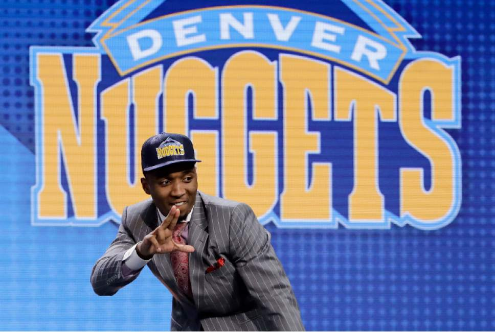 Donovan Mitchell reacts after being selected by the Denver Nuggets as the 13th pick overall during the NBA basketball draft, Thursday, June 22, 2017, in New York. (AP Photo/Frank Franklin II)