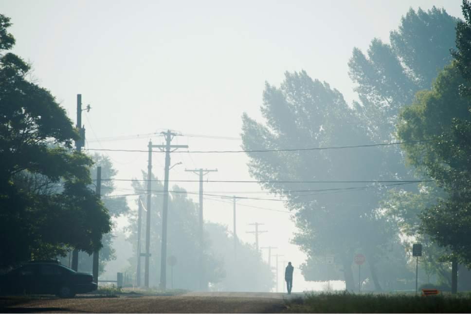 Rick Egan  |  The Salt Lake Tribune Haze from smoke of the Brian Head fire drifts through the streets of Parowan last week.
