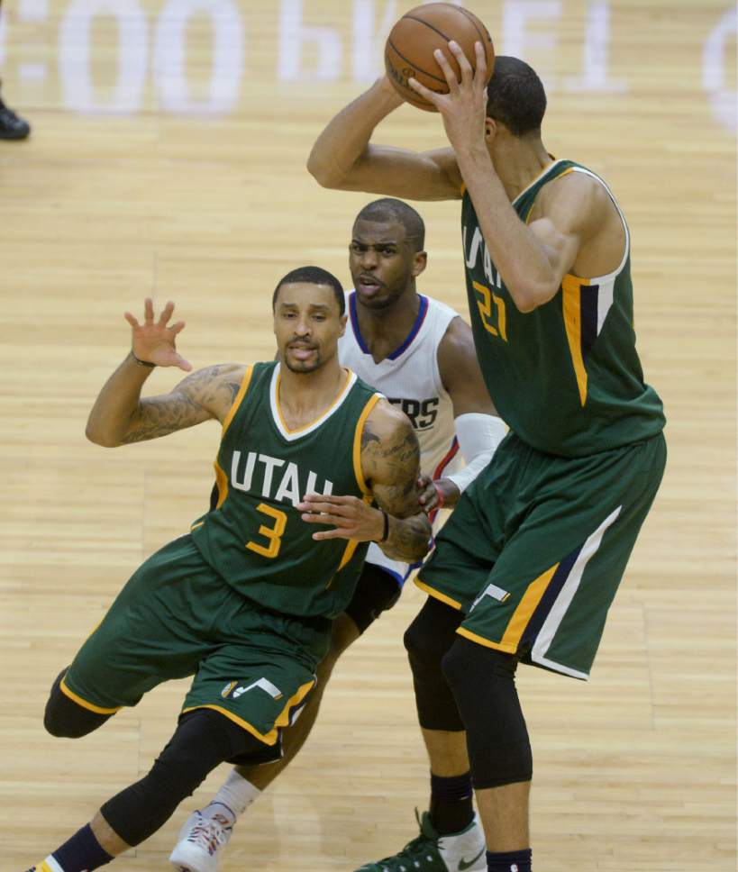 Steve Griffin  |  The Salt Lake Tribune   Utah Jazz center Rudy Gobert (27) holds the ball up as LA Clippers guard Chris Paul (3) chases Utah Jazz guard George Hill (3) during game 5 of the the Jazz versus Clippers NBA playoff game at the Staples Center in Los Angeles Tuesday April 25, 2017.
