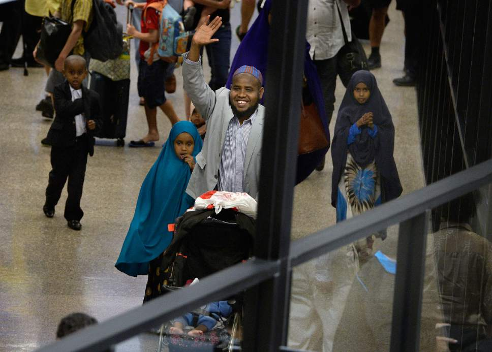 Scott Sommerdorf | The Salt Lake Tribune Imam Yussuf Awadir Abdi waves as he gets his first glimpse of friends and family that are waiting for him as he arrives at Salt Lake City International airport, Sunday, June 18, 2017.