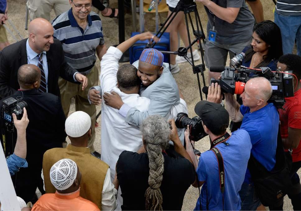Scott Sommerdorf | The Salt Lake Tribune Imam Yussuf Awadir Abdi gets hugs from friends and family as he arrives at Salt Lake City International airport, Sunday, June 18, 2017.