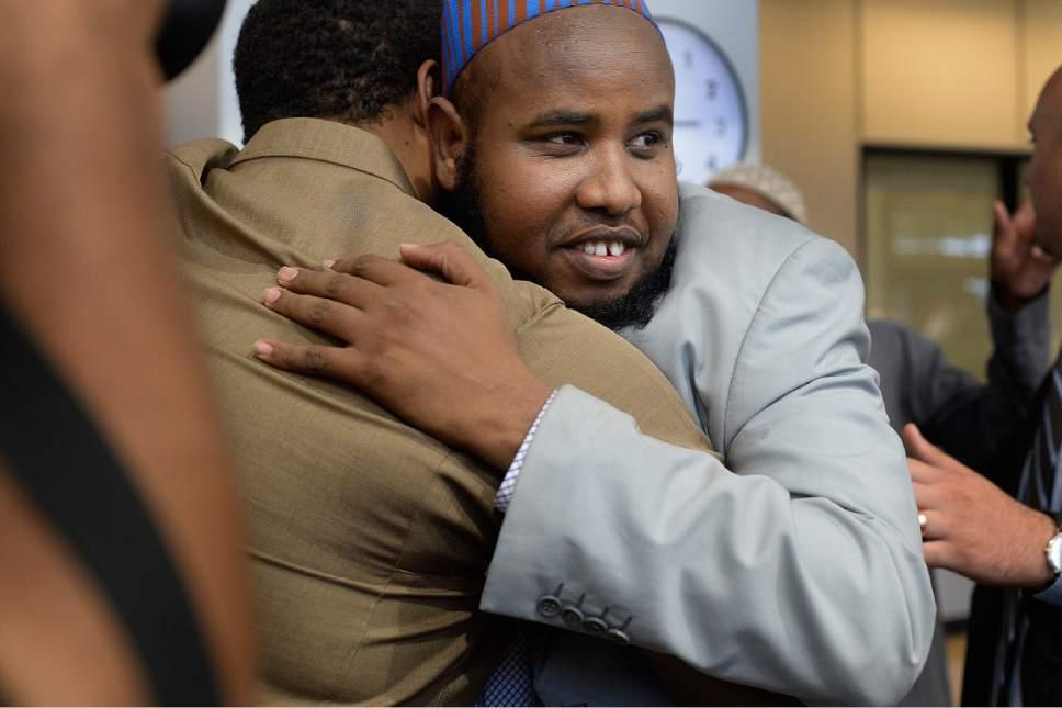 Scott Sommerdorf | The Salt Lake Tribune Imam Yussuf Awadir Abdi gets hugs from friends after he arrived at Salt Lake City International airport, Sunday, June 18, 2017.