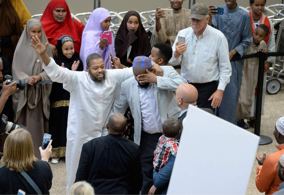 Scott Sommerdorf | The Salt Lake Tribune Imam Yussuf Awadir Abdi dabs his eyes as he is greeted by friends and family after he arrived at Salt Lake City International airport, Sunday, June 18, 2017.