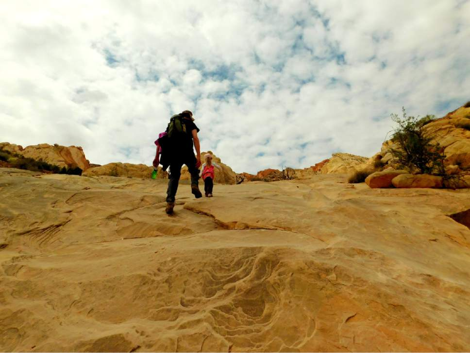 Erin Alberty  |  The Salt Lake Tribune  Father and daughter march up a slickrock slope May 1, 2016, near Moonshine Tanks in the San Rafael Swell.