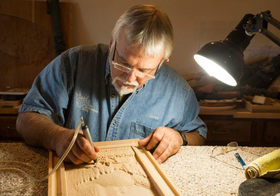 Rick Egan  |  The Salt Lake Tribune  Sculptor Steve Bartholomew works on a wood carving in the studio of his cabinet store in Cedar City. June 14, 2017.