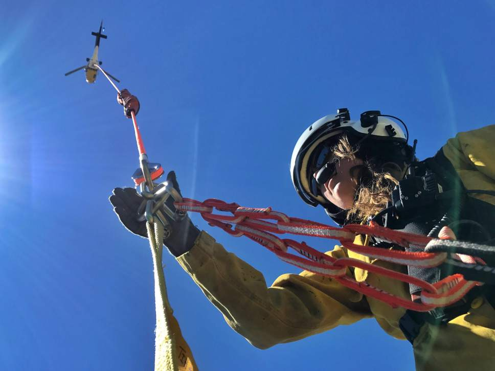 Photo courtesy of the Bureau of Land Management  A firefighter connects gear to one of nearly a dozen water-bearing helicopters at the Brian Head Fire.