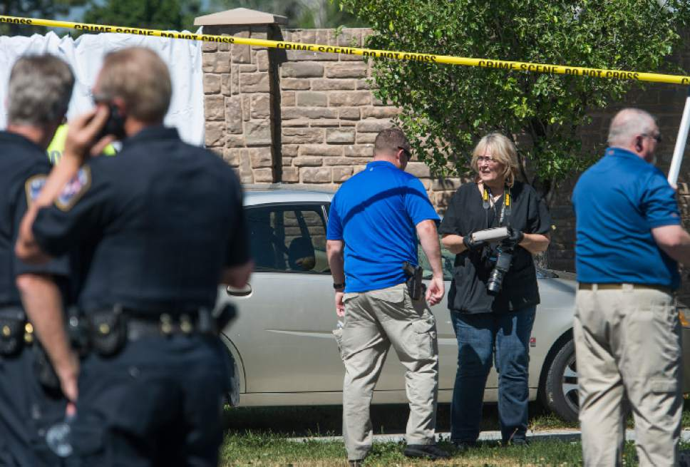 Leah Hogsten  |  The Salt Lake Tribune West Jordan Police investigator and photographer removes the victim's purse from her car at the scene where a woman is dead after a drive-by shooting incident in West Jordan on Wednesday morning. West Jordan police Sgt. Joe Monson said the woman, whose identity was not immediately released, was stopped at a stop light at Jaguar Drive (2700 West) and 7800 South, when at least one shot was fired into her car at 8:59 a.m.. Her car crashed into a wall and a tree a short distance later.  Monson confirmed the woman was found dead at the scene.