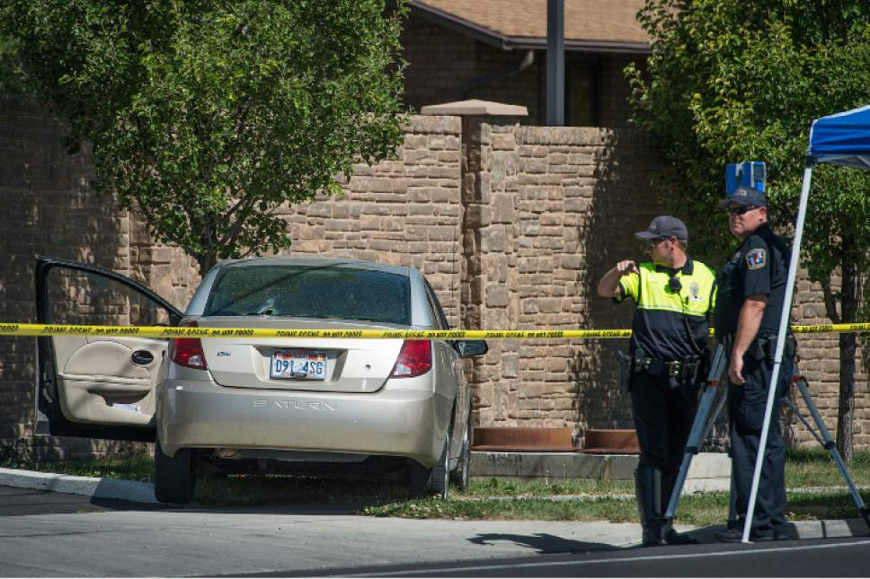 Leah Hogsten  |  The Salt Lake Tribune West Jordan Police investigate the scene where a woman is dead after a drive-by shooting incident in West Jordan on Wednesday morning at a stop light at Jaguar Drive and 7800 South, when at least one shot was fired into her car which crashed into a wall and a tree a short distance later. The victim's identity was not released.