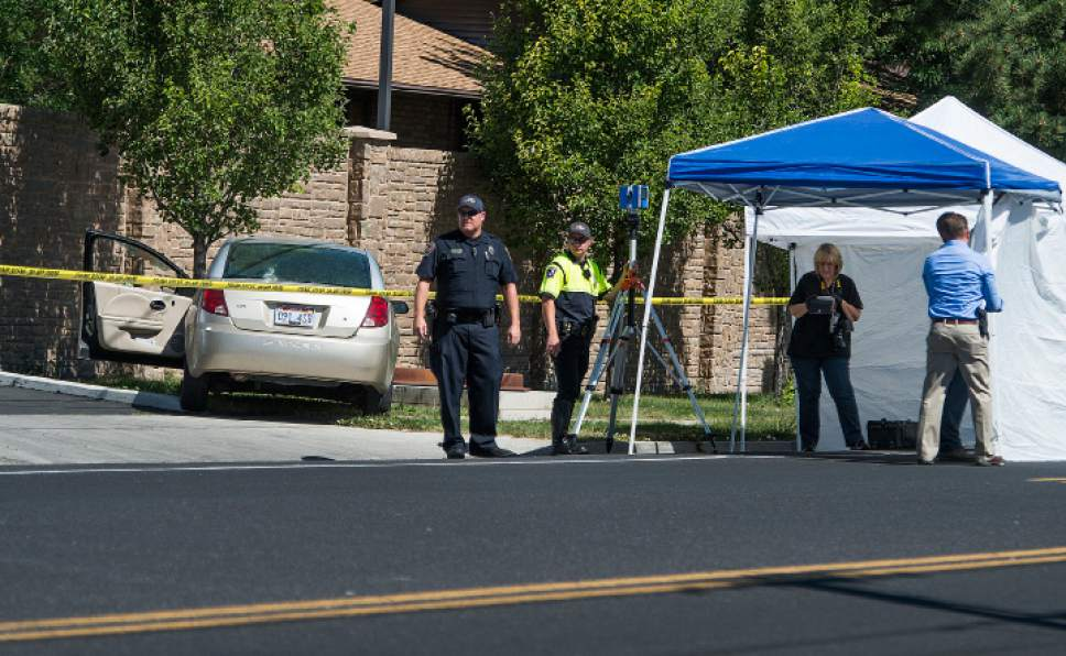 Leah Hogsten  |  The Salt Lake Tribune West Jordan Police investigate the scene where a woman is dead after a drive-by shooting incident in West Jordan on Wednesday morning. West Jordan police Sgt. Joe Monson said the woman, whose identity was not immediately released, was stopped at a stop light at Jaguar Drive (2700 West) and 7800 South, when at least one shot was fired into her car at 8:59 a.m.. Her car crashed into a wall and a tree a short distance later.  Monson confirmed the woman was found dead at the scene.