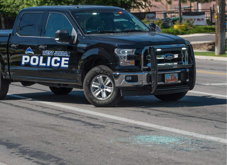 Leah Hogsten  |  The Salt Lake Tribune Broken glass lies at the intersection of Jaguar Drive (2700 West) and 7800 South in West Jordan. West Jordan Police investigate the scene where a woman is dead after a drive-by shooting incident in West Jordan on Wednesday morning. West Jordan police Sgt. Joe Monson said the woman, whose identity was not immediately released, was stopped at a stop light at Jaguar Drive (2700 West) and 7800 South, when at least one shot was fired into her car at 8:59 a.m.. Her car crashed into a wall and a tree a short distance later.  Monson confirmed the woman was found dead at the scene.