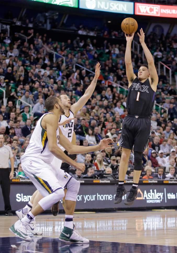 Phoenix Suns guard Devin Booker (1) shoots as Utah Jazz's Joe Ingles (2) and Rudy Gobert, left, defend in the first half during an NBA basketball game Saturday, Dec. 31, 2016, in Salt Lake City. (AP Photo/Rick Bowmer)