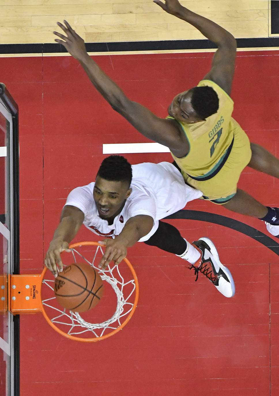 Louisville's Donovan Mitchell (45) dunks past the defense of Notre Dame's T.J. Gibbs (2) during the second half of an NCAA college basketball game, Saturday, March 4, 2017, in Louisville, Ky. Louisville won 71-64. (AP Photo/Timothy D. Easley)