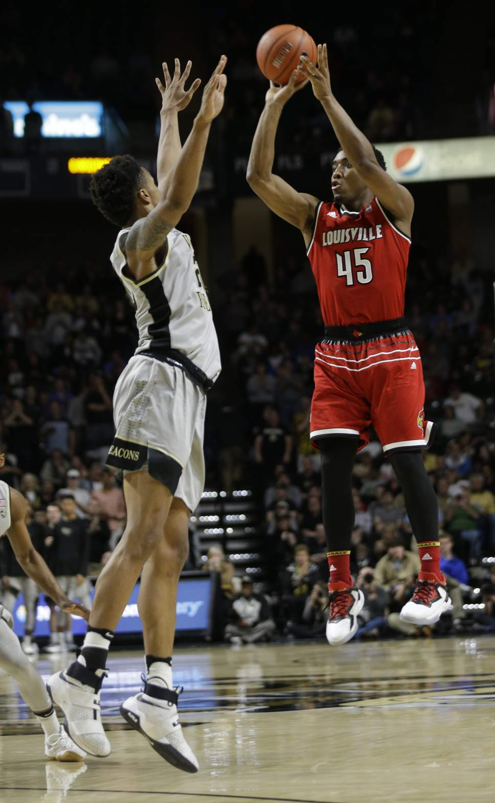 Louisville's Donovan Mitchell (45) shoots over Wake Forest's John Collins (20) in the second half of an NCAA college basketball game in Winston-Salem, N.C., Wednesday, March 1, 2017. Wake Forest won 88-81. (AP Photo/Chuck Burton)