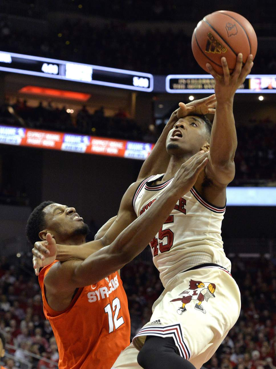 Louisville's Donovan Mitchell (45) is fouled by Syracuse's Taurean Thompson (12) during the second half of an NCAA college basketball game, Sunday, Feb. 26, 2017, in Louisville, Ky. (AP Photo/Timothy D. Easley)