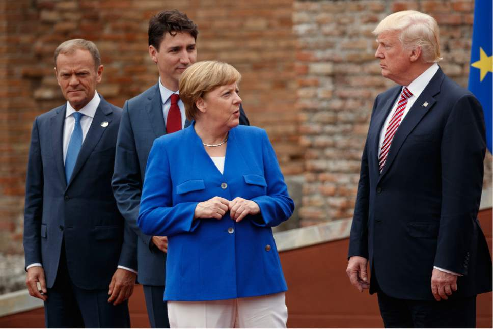 FILE - In this May 26,m 2017 file photo, German Chancellor Angela Merkel, accompanied by European Council President Donald Tusk, Canadian Prime Minister Justin Trudeau, talks with President Donald Trump during a family photo with G7 leaders at the Ancient Greek Theater of Taormina in Taormina, Italy. President Donald Trump will learn this week whether he gets a second chance to make a first impression as he returns to Europe and has his first encounter with Russia's Vladimir Putin.  (AP Photo/Evan Vucci, File)