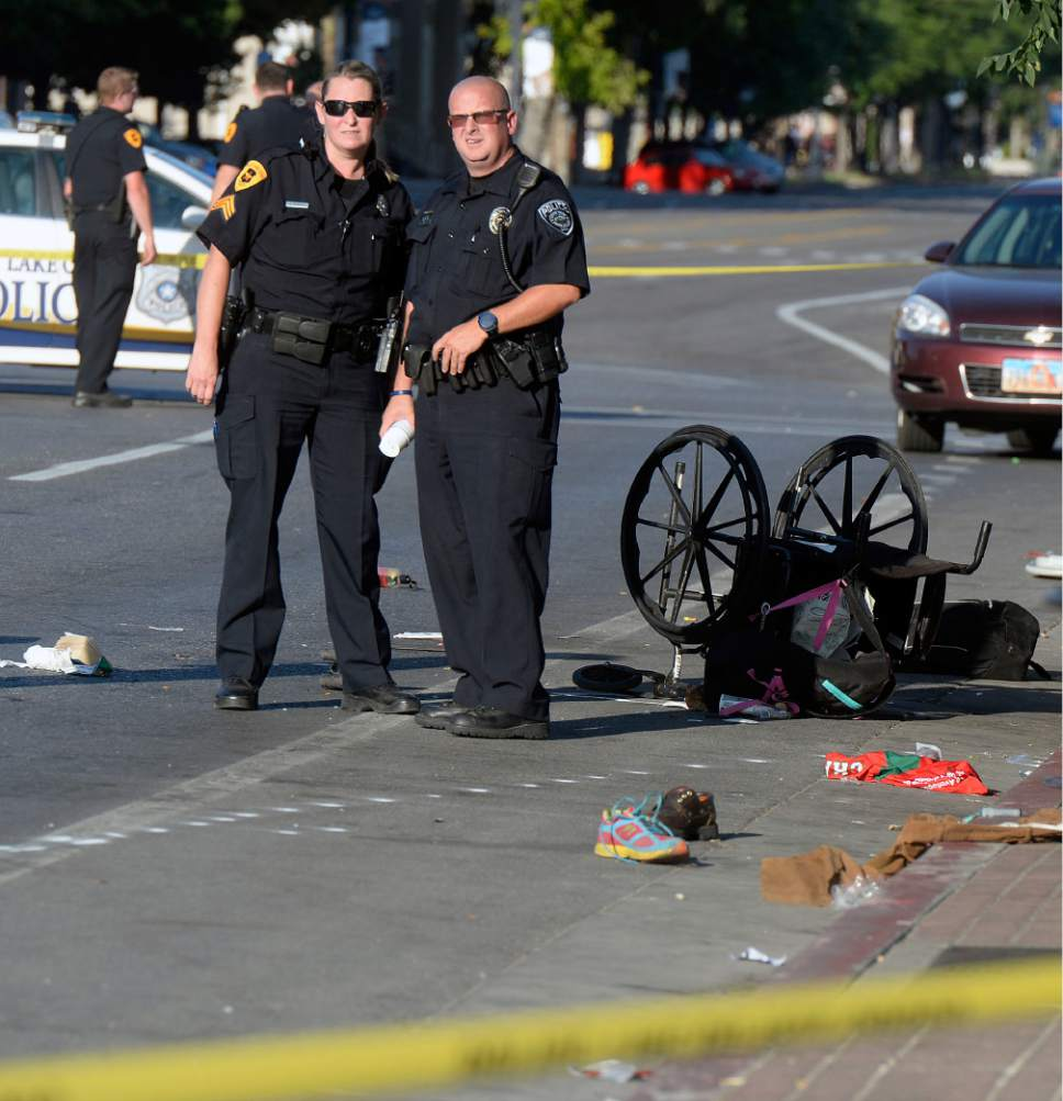 Al Hartmann  |  The Salt LakeTribune   Salt Lake City Police investigate the scene of a car crash at 465 West on 200 South that left one pedestrian dead and five others injured on Tuesday, July 4, 2017. The driver, a woman wearing a red tank top, fled the scene after the car drove onto the sidewalk Tuesday evening.