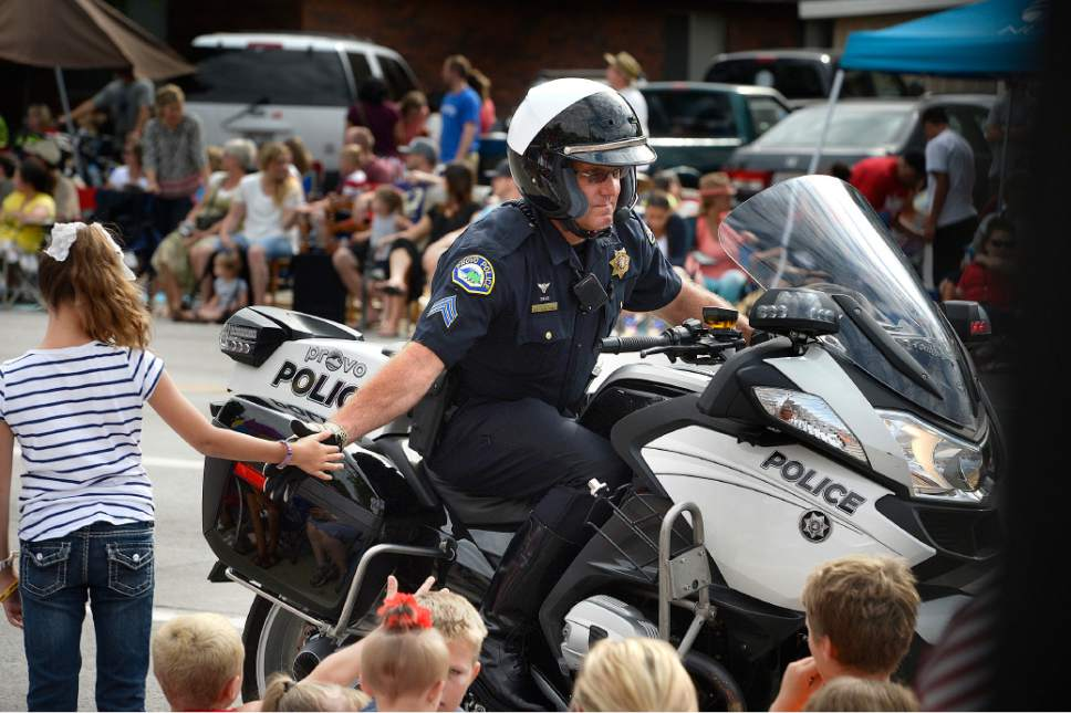 Scott Sommerdorf   |   Tribune file photo A little girl gets a high five from a Provo motorcycle policeman as he drives by during the Fourth of July Parade in Provo, Saturday, July 4, 2015.