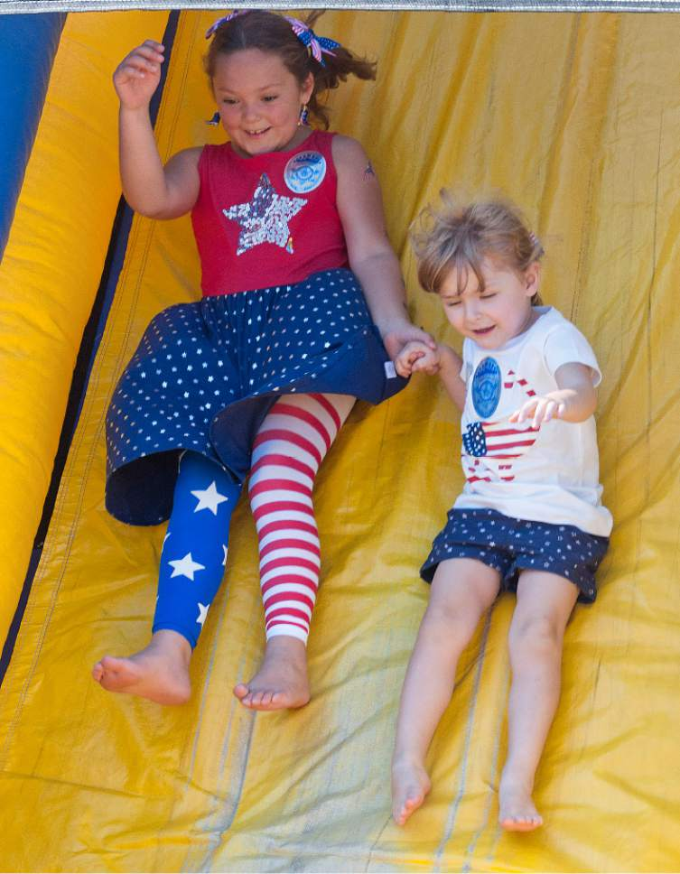 Michael Mangum  |  Special to the Tribune  6 year old Zeybri Symes, left, and 3 year old Gianna Graves, from Holladay, slide to the bottom of a bouncy house obstacle course during an Independence Day carnival on Tuesday, July 4th, 2017 at Evergreen Park in Millcreek.