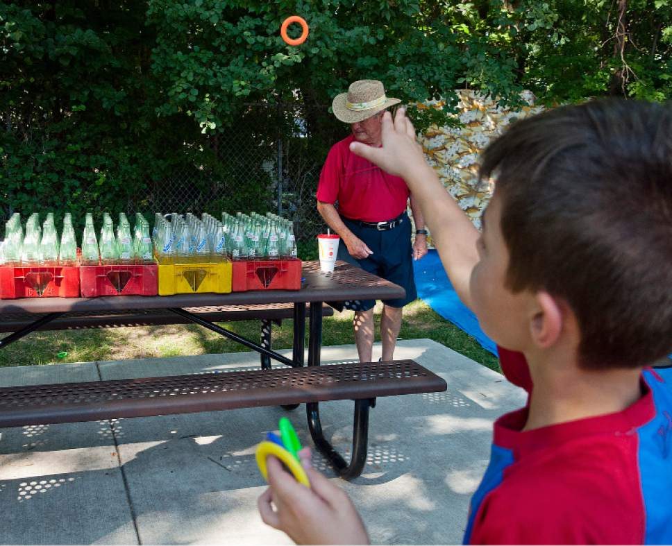 Michael Mangum  |  Special to the Tribune  Carter Thomas, 9 years old, from Holladay, plays a ring toss game during an Independence Day carnival on Tuesday, July 4th, 2017 at Evergreen Park in Millcreek.
