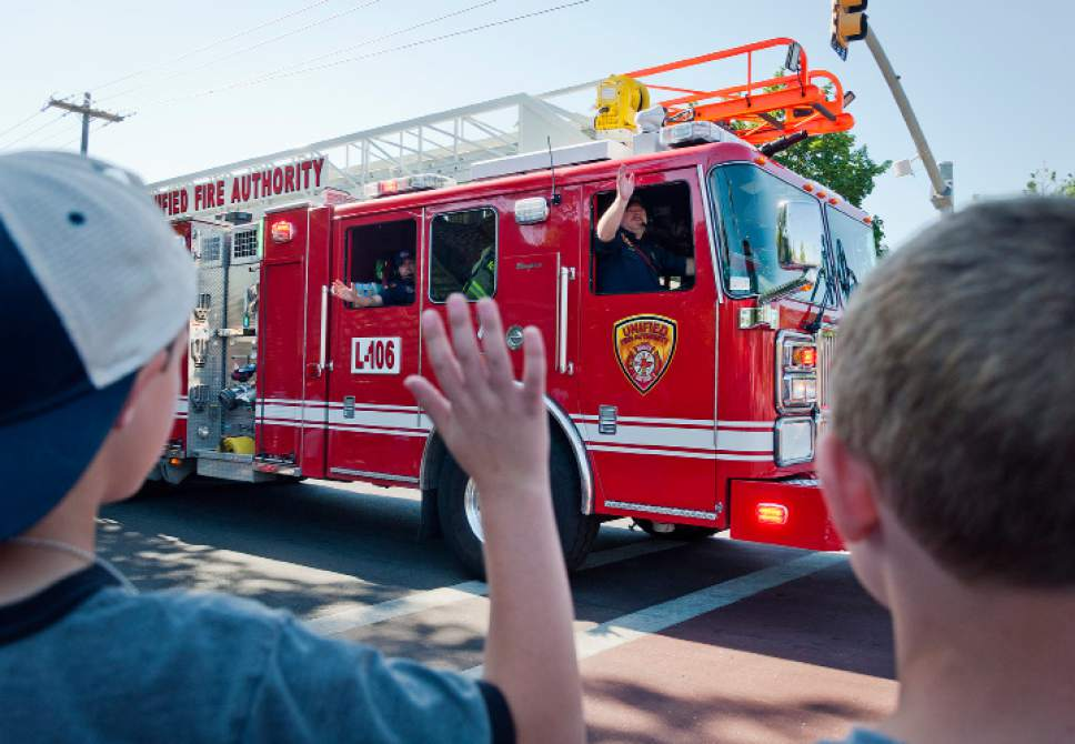 Michael Mangum  |  Special to the Tribune  Kids wave to a Unified Fire Authority truck during an Independence Day parade on Tuesday, July 4th, 2017 in Millcreek.