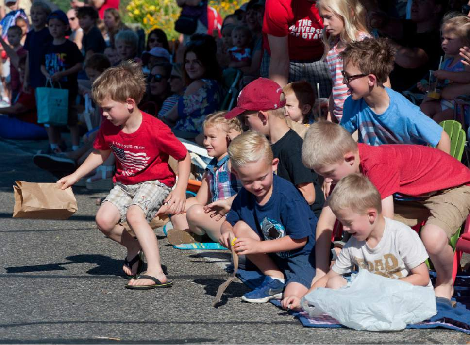 Michael Mangum  |  Special to the Tribune  Children rush to gather candy during an Independence Day parade on Tuesday, July 4th, 2017 in Millcreek.