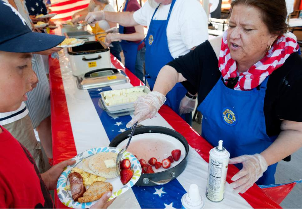 Michael Mangum  |  Special to the Tribune  Donna Sparks Williams of Salt Lake City serves up strawberries and cream to Nathan Davis, 8 years old, of Millcreek, during an Independence Day celebration on Tuesday, July 4th, 2017 at Evergreen Park in Millcreek.