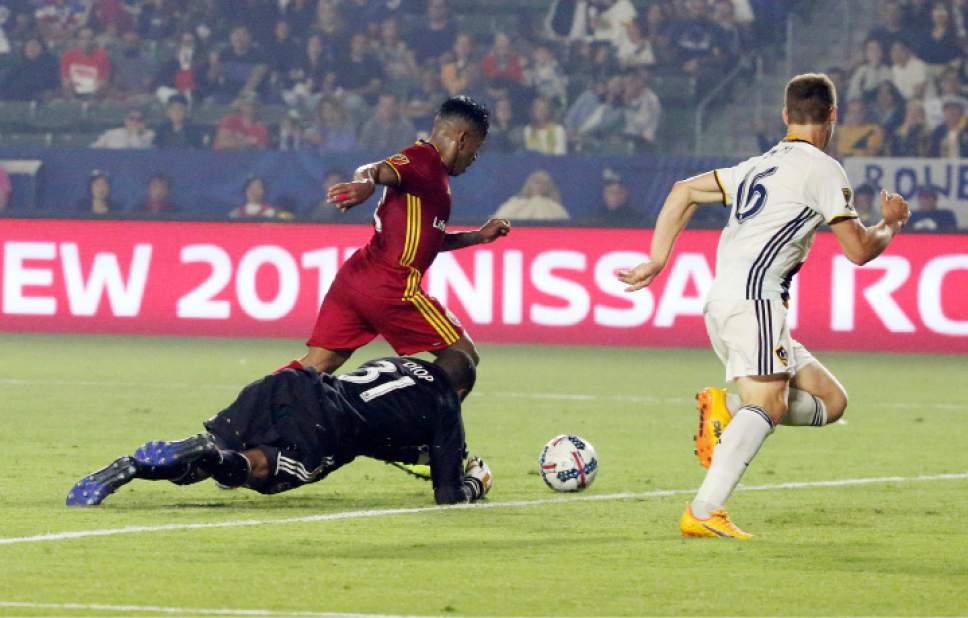 Real Salt Lake forward Joao Plata (10) goes past downed LA Galaxy goalkeeper Clement Diop (31) and forward Ariel Lassiter (15) to score the goal in the second half of an MLS soccer match in Carson, Calif., Tuesday, July 4, 2017. Real Salt Lake won, 6-2. (AP Photo/Reed Saxon)