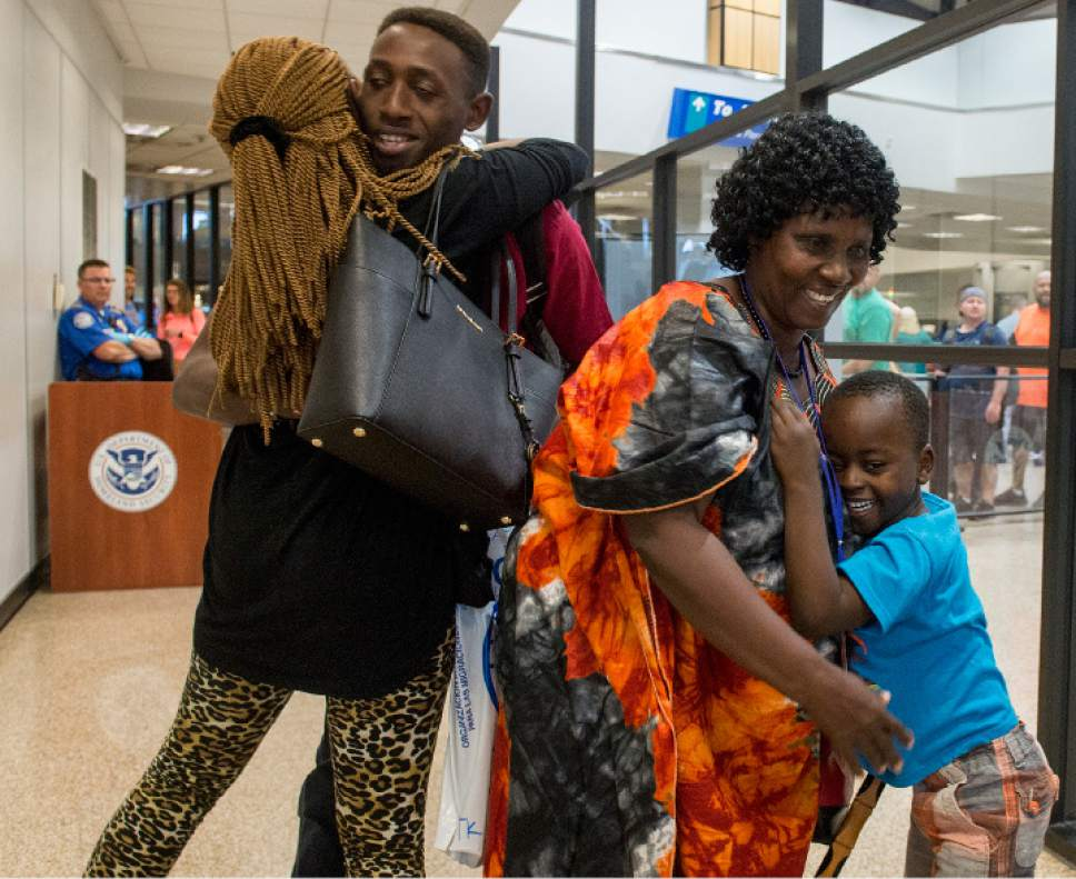 Leah Hogsten  |  The Salt Lake Tribune   l-r Aimee Ingabire hugs her brother Patrick Byusa moments after his arrival to Salt Lake City with his mother Jullien Mukantagara (right, hugging an unidentified child) and four other siblings from the Democratic Republic of Congo. The Salt Lake City office of the International Rescue Committee welcomed the last refugee family to Utah on Thursday,  July 6, 2017, before President Donald Trump's 120-day ban on refugees goes into effect.