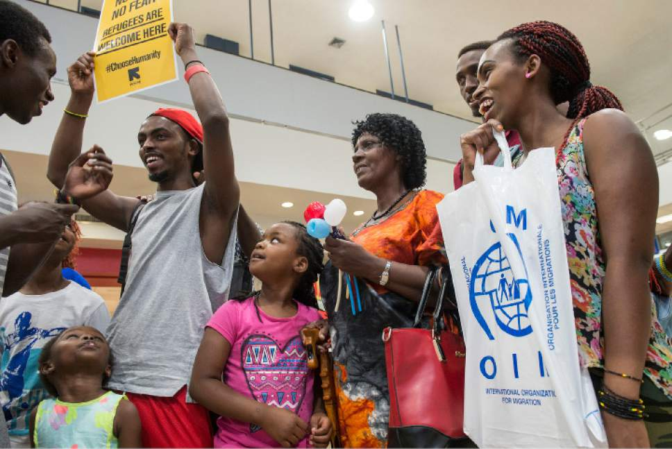 Leah Hogsten  |  The Salt Lake Tribune  Jullien Mukantagara, (center, in orange) smiles as fellow family friend Patient Gatabazi (left) holds a welcoming sign for Mukantagara and her children from the Democratic Republic of Congo, moments after their arrival in Utah where the entire family was reunited. The Salt Lake City office of the International Rescue Committee welcomed the last refugee family to Utah,  July 6, 2017, before President Donald Trump's 120-day ban on refugees goes into effect.