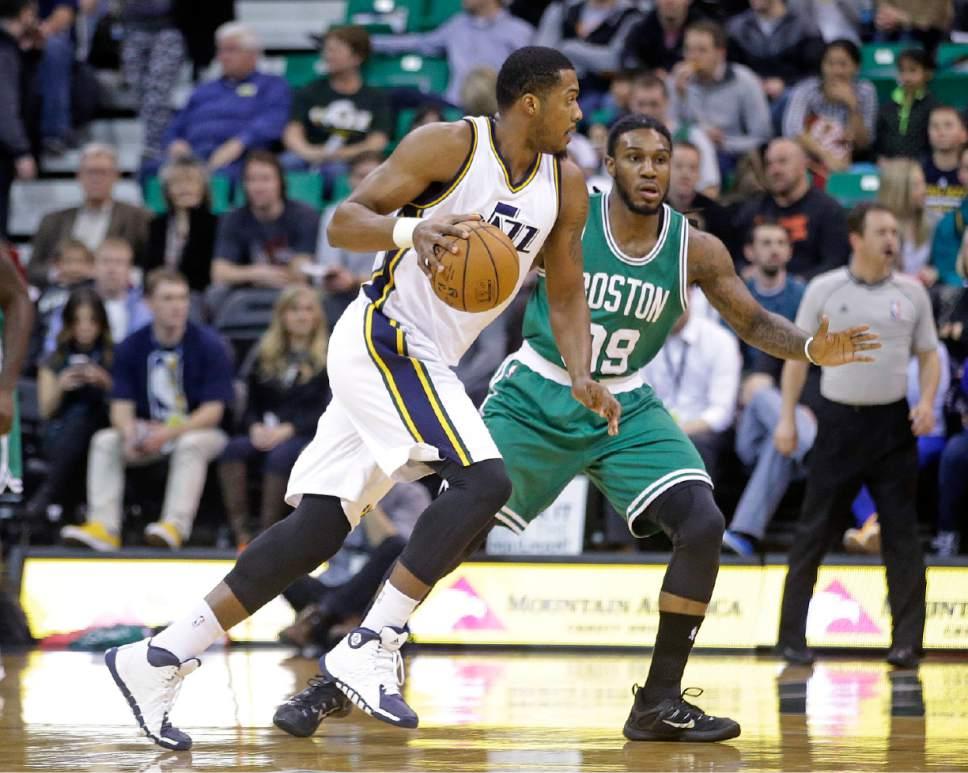 Utah Jazz forward Derrick Favors, left, drives as Boston Celtics forward Jae Crowder (99) defends in the first quarter during an NBA basketball game Monday, Jan. 26, 2015, in Salt Lake City.  (AP Photo/Rick Bowmer)