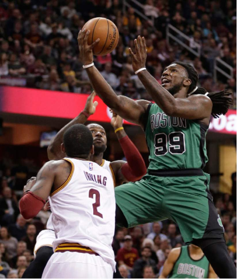 Boston Celtics' Jae Crowder (99) drivers to the basket against Cleveland Cavaliers' Kyrie Irving (2) and LeBron James (23) in the first half of an NBA basketball game Saturday, March 5, 2016, in Cleveland. (AP Photo/Tony Dejak)