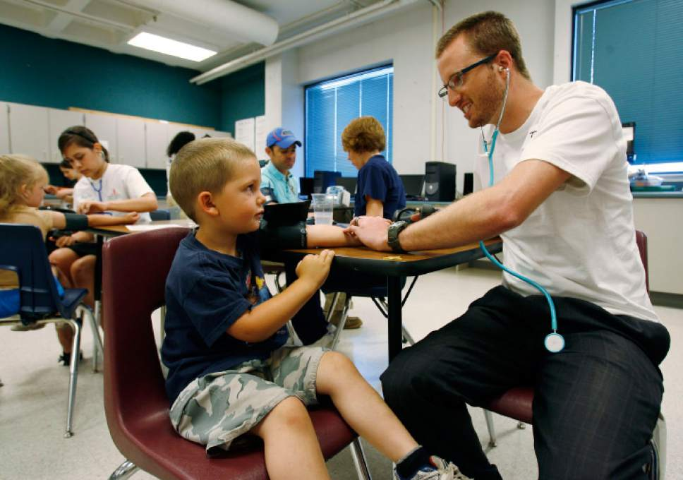 Steve Griffin  |  The Salt Lake Tribune  Health care volunteer Thom Haslam checks the vital signs of 4-year-old Skylar Dumas at the 18th annual Junior League Care Fair at Horizonte Center in Salt Lake City Friday, July 9, 2010.