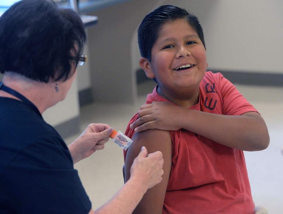 Al Hartmann     The Salt Lake Tribune  Alexis Herrera, 11, cracks a smile after getting an immunization shot for school at the Junior League CARE Fair in the Horizonte Center in Salt Lake City Friday, July 15, 2016.