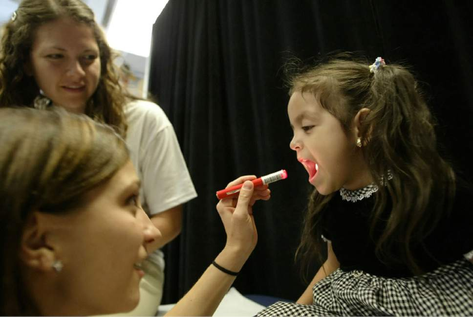 Chris Detrick  |  Salt Lake Tribune  Carla Citlaly Moreno, 4, of Salt Lake City, gets her tonsils checked by University of Utah medical student Melinda Liddle, foreground, and Angela DeLao during at a health clinic sponsored by the Junior League of Salt Lake on August 13, 2005.