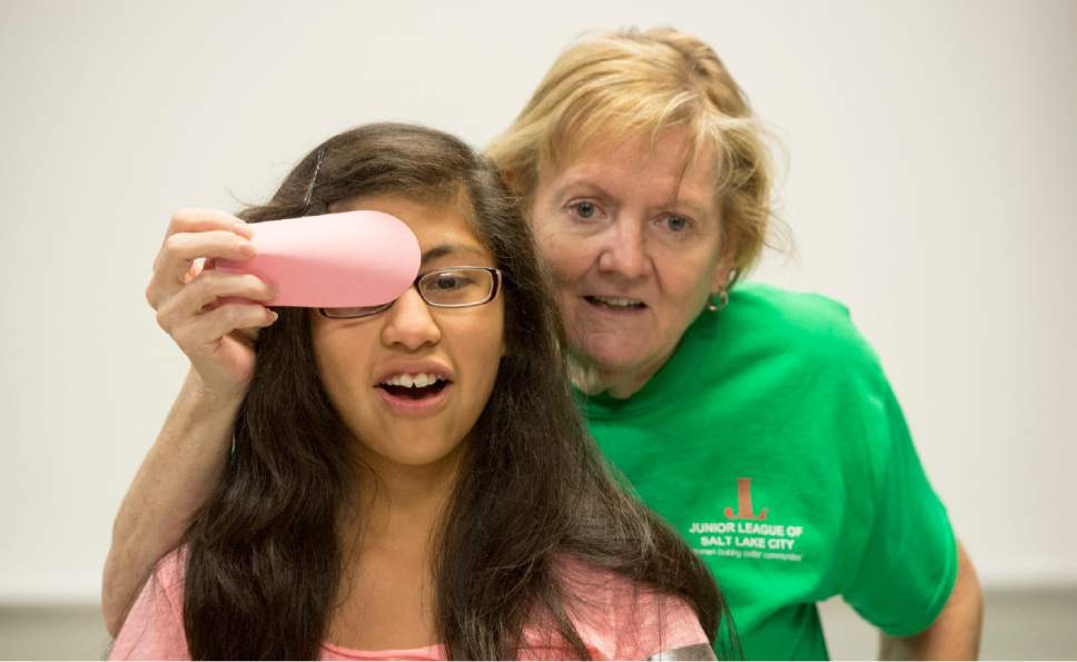 Rick Egan     The Salt Lake Tribune  Gayle Linford gives Jade Zamaora, 11, an eye examination at the Horizonte Training Center during the 23rd Annual Community Assistance & Resource Event, or CARE Fair, organized by The Junior League of Salt Lake City, Saturday, July 11, 2015.