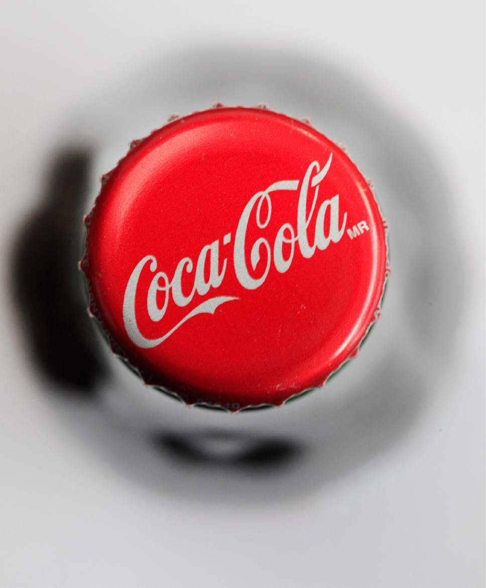 This April 25, 2011 photo shows  a bottle cap on a bottle of Coca-Cola in Philadelphia. Coca-Cola reported a quarterly profit Wednesday, April 22, 2015,  that beat Wall Street expectations as the world's largest beverage maker worked on trimming costs and sold more drinks. The maker of Sprite, Dasani, Powerade and other drinks said its global volume rose 1 percent, reflecting gains in both soda and non-carbonated drinks. (AP Photo/Matt Rourke)