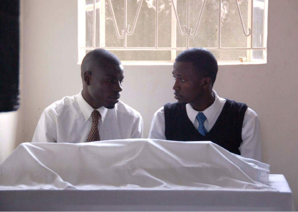 Buteera Faustin, right, and Emma Kakande chat at an LDS sacrament table in Seeta, Uganda, before the service begins. Mormon growth is surging in parts of Africa. Courtesy of Michael Stack.