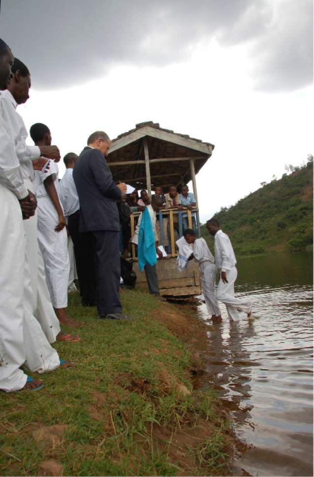 Recently baptized LDS converts exit the water at Lake Muhazi, Rwanda, as Uganda/Kampal Mission President Edward Christensen  (blue suit) and a crowd look on with approval. Mormon growth is surging in parts of Africa. Courtesy Mike Stack.
