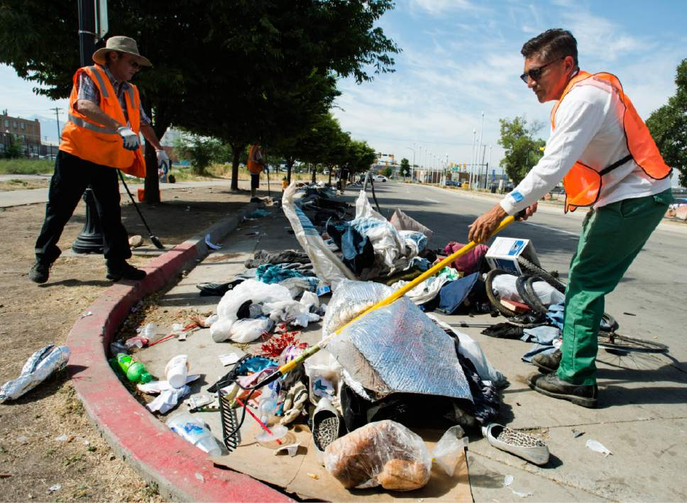 Rick Egan  |  The Salt Lake Tribune  Jorge Mendez, right, of the Salt Lake County Health Department, cleans up trash left by homeless campers on 500 West in Salt Lake City on Thursday, July 6, 2017. The health department does a cleanup in the area every other week or so. The biggest challenge for crews is the disposal of syringes discarded by drug users.
