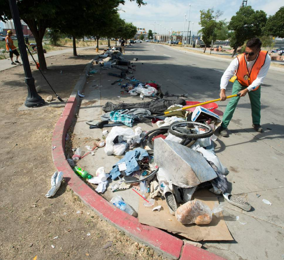 Rick Egan  |  The Salt Lake Tribune  Jorge Mendez, of the Salt Lake County Health Department, cleans up trash left by homeless campers on 500 West in Salt Lake City on Thursday, July 6, 2017. The health department does a cleanup in the area every other week or so. The biggest challenge for crews is the disposal of syringes discarded by drug users.
